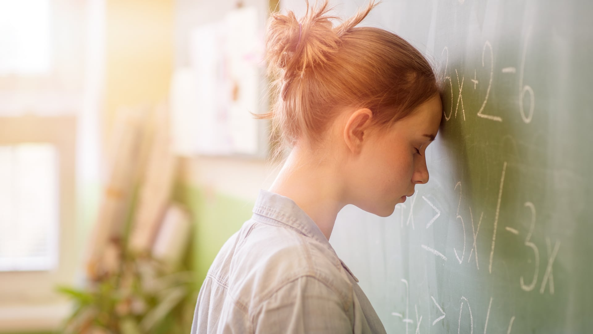 An anxious teenage girl with red hair pressing her head against a blackboard filled with maths - anxious teen
