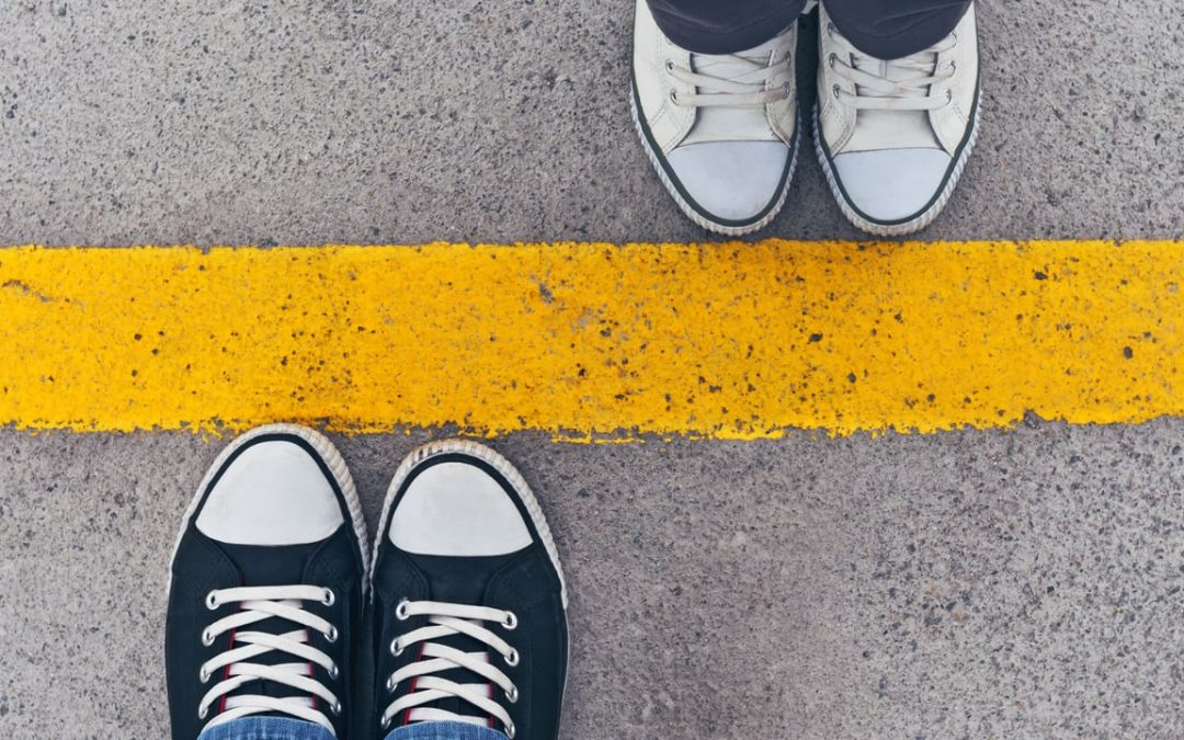 boundaries - humanism bypass - a yellow line between two pairs for feet in trainers