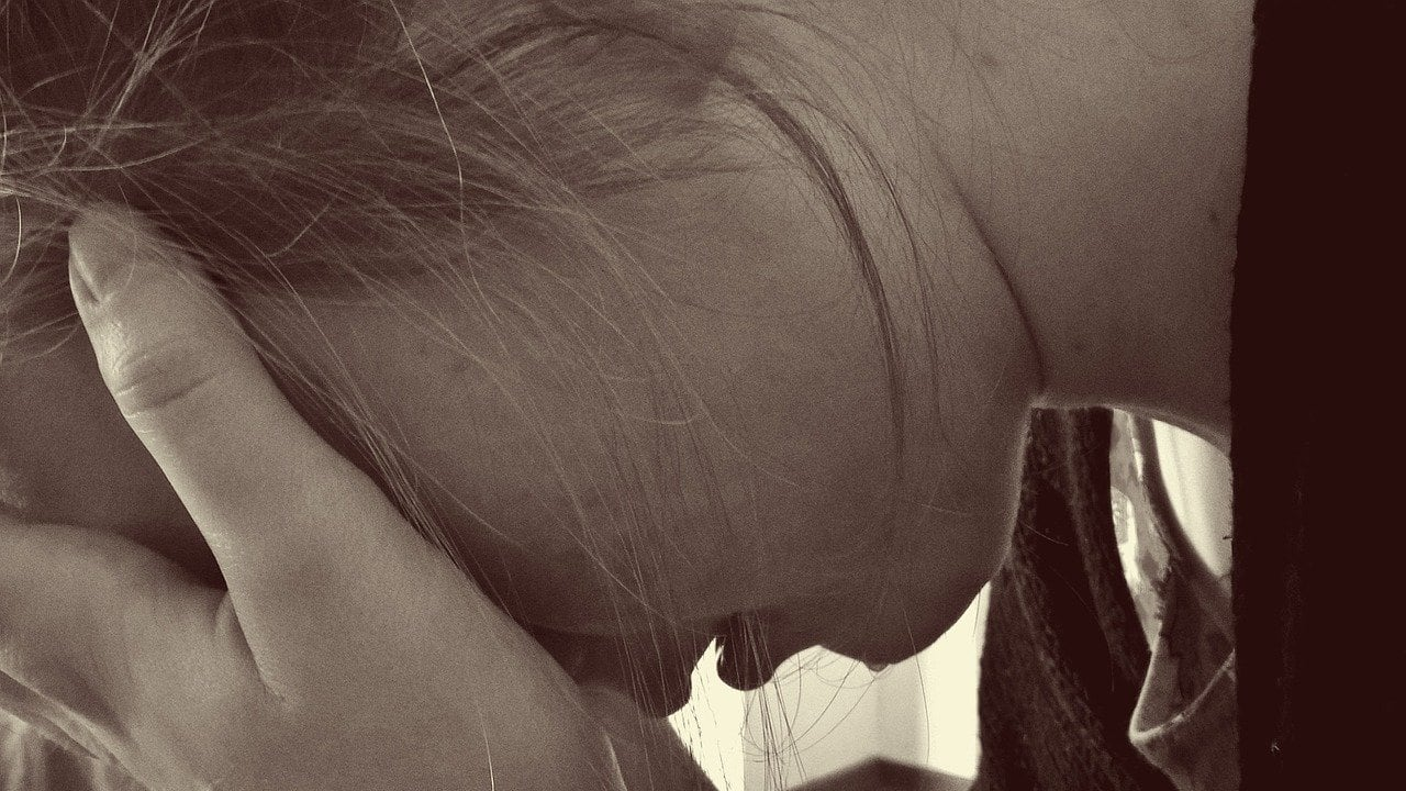A sad young woman holding her head in her hands - Support Your Teen Through a Breakup