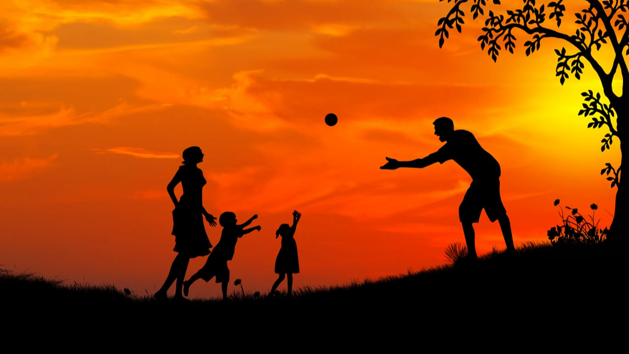 A family playing together silhouetted against a red sunset - family playtime