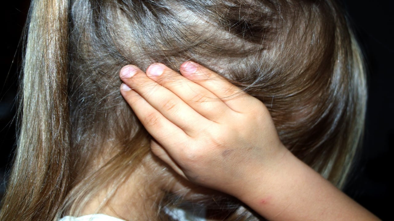 a blonde girl covering her ears - Help Your Child Cope with divorce