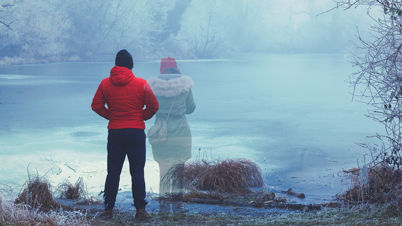 Lonely man in red jacket standing by the lake in winter, with transparent woman figure standing next to him - loss - All is Well