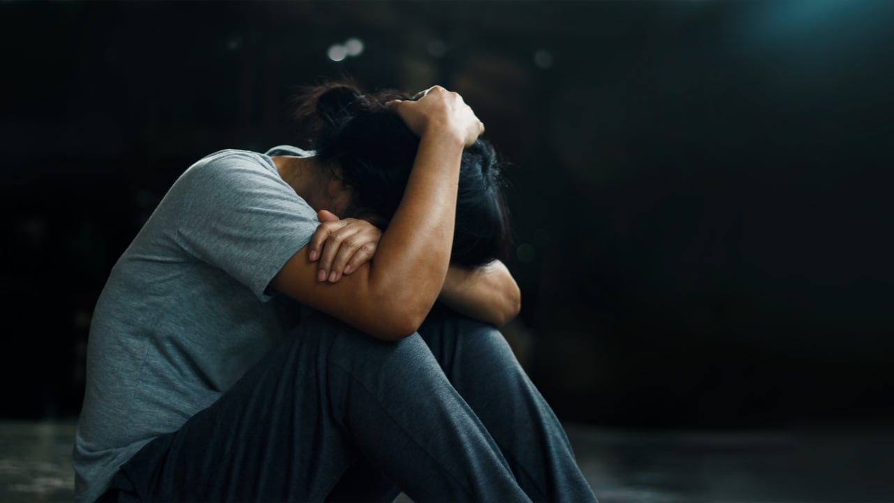 A distressed woman sitting with her knees up and her head in her arms - Understanding PTSD