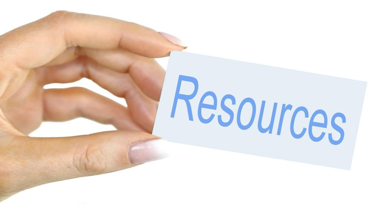 Resources written on a card held in a female left hand