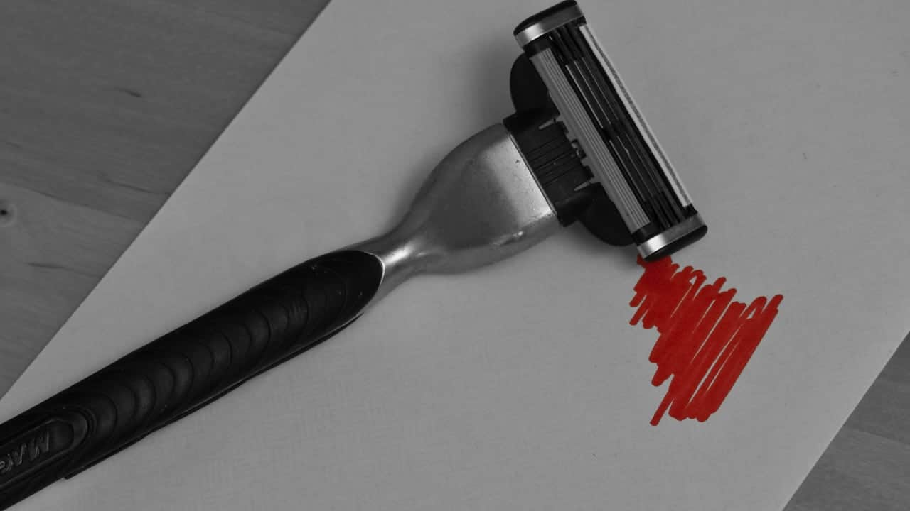 A razor resting on a sheet of paper with red 'blood' drawn by it - Self-Harm Is Not Uncommon in Children