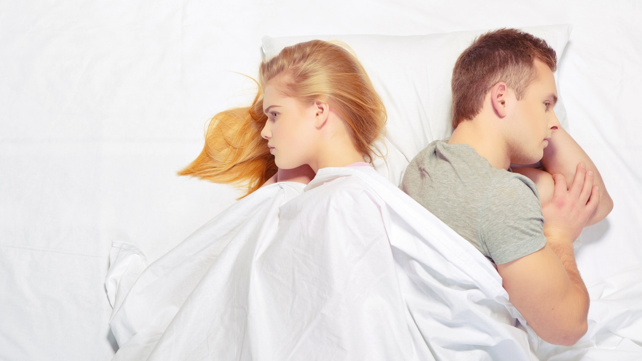 sexual dysfunction - a young mans and woman in bed, back to back, looking angry, unhappy and frustrated