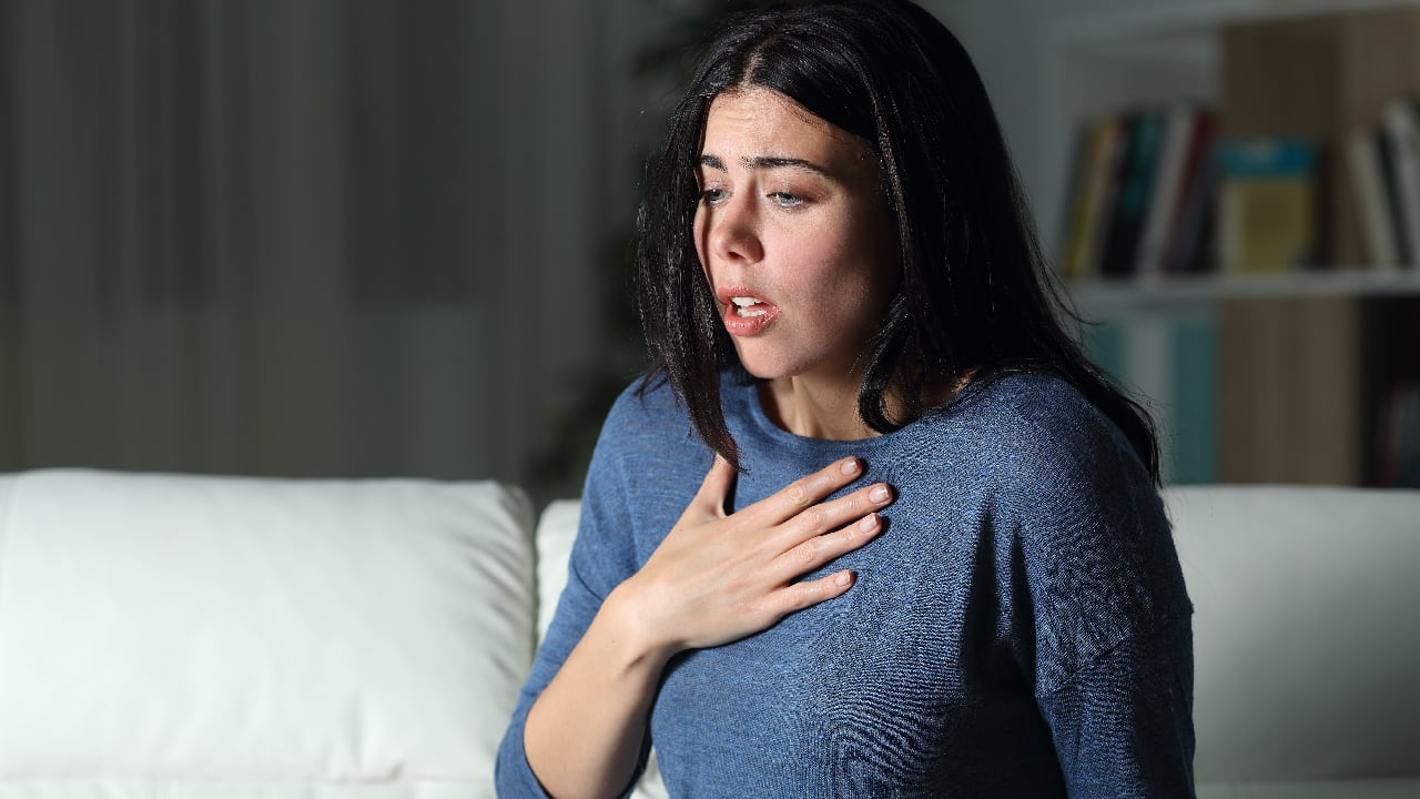 An anxious woman clutching her chest - physical symptoms of anxiety