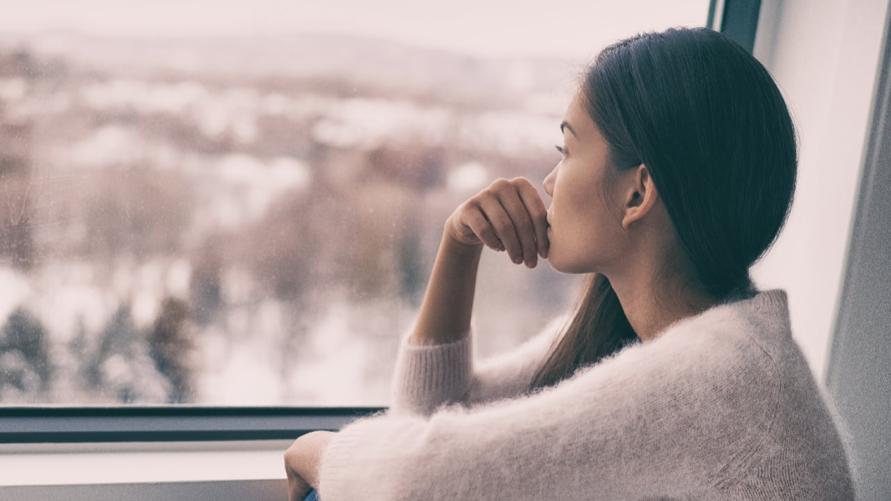 A thoughtful woman looking out of a window - signs of depression